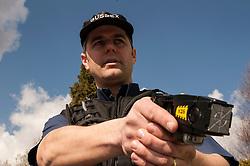 Armed police officer with a taser gun UK