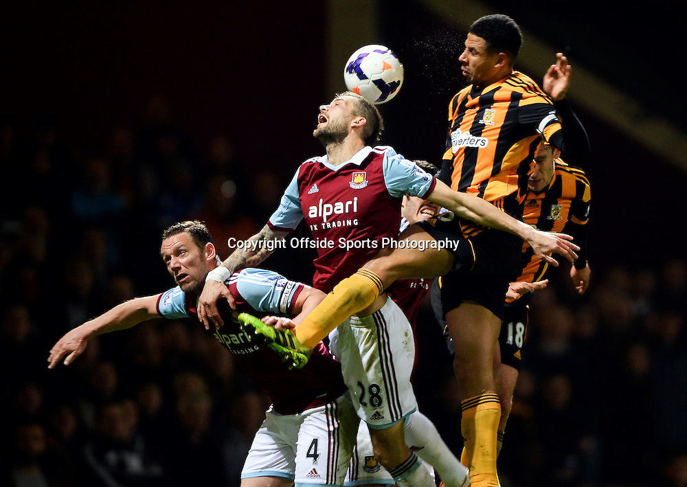 26 March 2014 - Barclays Premier League - West Ham United v Hull City - Kevin Nolan and Roger Johnson of West Ham United tangle with Curtis Davis of Hull City - Photo: Marc Atkins / Offside.