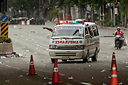 16 MAY 2010 - BANGKOK, THAILAND: An ambulance carrying a sniper's victim and a motorcycle taxi evacuating a civilian try to get off of Rama IV Road in Bangkok Sunday. Thai troops and anti government protesters clashed on Rama IV Road again Sunday afternoon in a series of running battles. Troops fired into the air and unidentified snipers shot at pedestrians on the sidewalks. At one point Sunday the government said it was going to impose a curfew only to rescind the announcement hours later. The situation in Bangkok continues to deteriorate as protests spread beyond the area of the Red Shirts stage at Ratchaprasong Intersection. Many protests now involve people who have not been active in the Red Shirt protests and live in the vicinity of Khlong Toei slum and Rama IV Road. Red Shirt leaders have called for a cease fire, but the government indicated that it is going to go ahead with operations to isolate the Red Shirt camp and clear the streets.      PHOTO BY JACK KURTZ