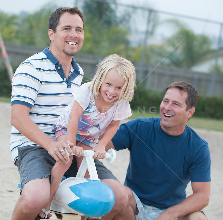 two men and their little girl enjoying time together in a playground