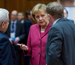 Angela Merkel, Germany's chancellor, center, speaks with Dimitris Christofias, president of Cyprus, left, and Lars Lokke Rasmussen, Denmark's prime minister, during the European Summit, in Brussels, on Friday, March 26, 2010. (Photo © Jock Fistick)