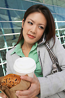 Businesswoman using mobile phone holding food and drink, outside office building