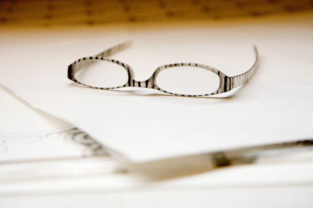 fashionable reading glasses laying on a piece of blank white paper