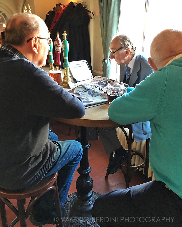 Three men drink a pint of bitter before indulging in the Sunday Roast lunch at The Tickell Arms pub in the village of Whittlesford in Cambridgeshire. Together with the traditional reading of the Sunday Times and other Sunday newspapers an iPad joined the group.
