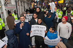 Brick Lane, London, December 13th 2013. Anjem Choudary, with microphone, leads his  'Sharia Project' as they demonstrate in Brick Lane against the consumption of Alchohol, blaming society's ills on drinking, and demanding that strict Sharia law be imposed to replace 'man-made' laws.