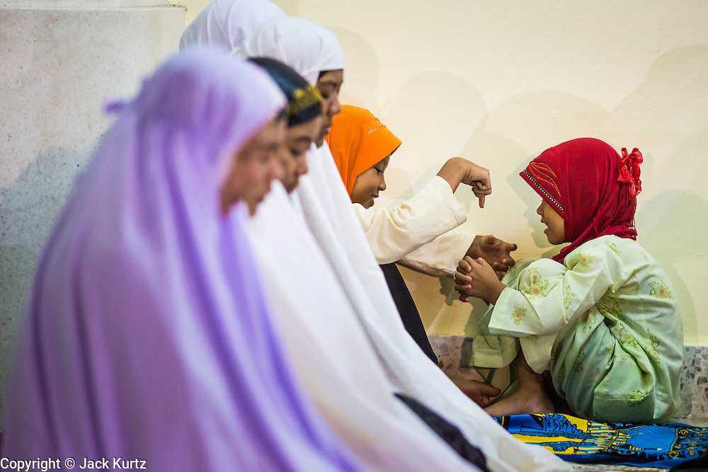 09 JULY 2013 - PATTANI, PATTANI, THAILAND:  Children play while a group of women pray in Pattani Central Mosque in Pattani, Thailand, Tuesday night on the first night of Ramadan. Ramadan is the ninth month of the Islamic calendar, and the month in which Muslims believe the Quran was revealed. Muslims believe that the Quran was sent down during this month, thus being prepared for gradual revelation by Jibraeel (Gabriel) to the Prophet Muhammad. The month is spent by Muslims fasting during the daylight hours from dawn to sunset. Fasting during the month of Ramadan is one of the Five Pillars of Islam.   PHOTO BY JACK KURTZ