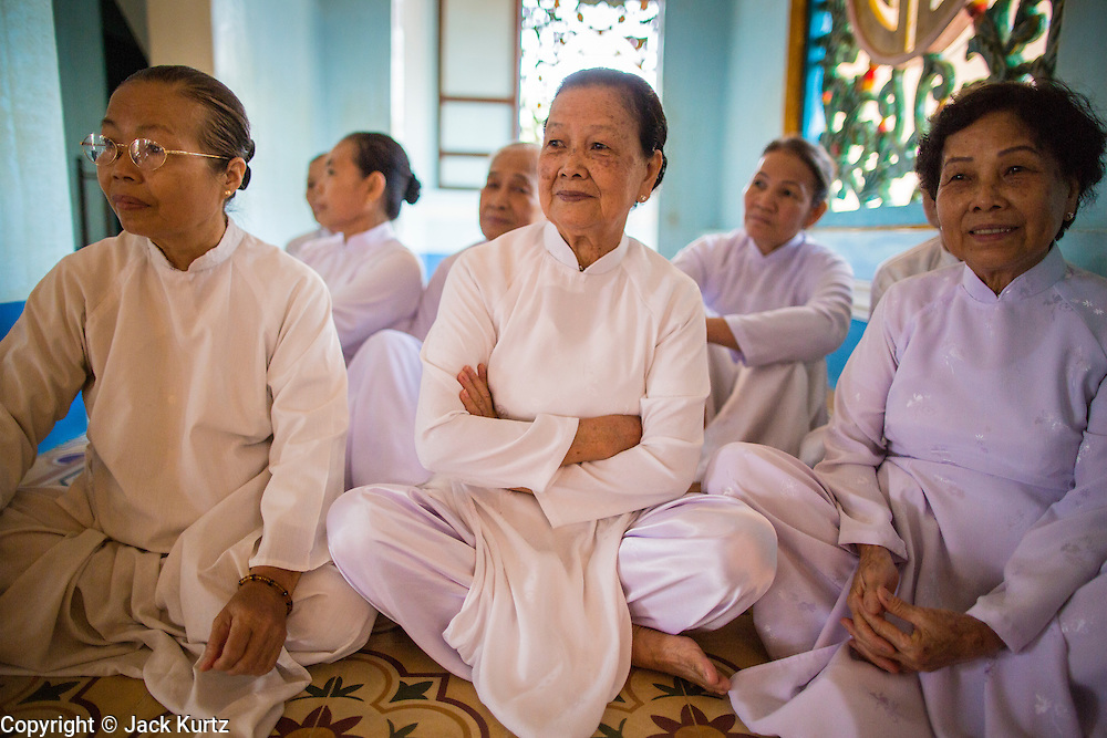 "29 MARCH 2012 - TAY NINH, VIETNAM:  Women in the Cao Dai wait for noon prayers to start at the Cao Dai Holy See in Tay Ninh, Vietnam. Cao Dai (also Caodaiism) is a syncretistic, monotheistic religion, officially established in the city of Tây Ninh, southern Vietnam in 1926. Cao means ""high"" and ""Dai"" means ""dais"" (as in a platform or altar raised above the surrounding level to give prominence to the person on it). Estimates of Cao Dai adherents in Vietnam vary, but most sources give two to three million, but there may be up to six million. An additional 30,000 Vietnamese exiles, in the United States, Europe, and Australia are Cao Dai followers. During the Vietnam's wars from 1945-1975, members of Cao Dai were active in political and military struggles, both against French colonial forces and Prime Minister Ngo Dinh Diem of South Vietnam. Their opposition to the communist forces until 1975 was a factor in their repression after the fall of Saigon in 1975, when the incoming communist government proscribed the practice of Cao Dai. In 1997, the Cao Dai was granted legal recognition. Cao Dai's pantheon of saints includes such diverse figures as the Buddha, Confucius, Jesus Christ, Muhammad, Pericles, Julius Caesar, Joan of Arc, Victor Hugo, and the Chinese revolutionary leader Sun Yat-sen. These are honored at Cao Dai temples, along with ancestors.    PHOTO BY JACK KURTZ"