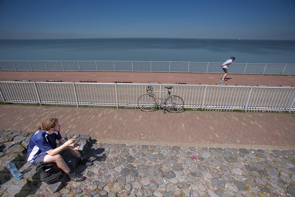 Een fietser pauzeert bij het monument op de Afsluitdijk, terwijl een man op skeelers voorbijkomt.. In 1932 werd de opening tussen de Waddenzee en de toenmalige Zuiderzee gesloten. Nu is het een belangrijke verkeersader tussen Friesland en Noord-Holland en scheidt het de Waddenzee met het IJsselmeer.<br /> <br /> A cyclist is pausing at the Afsluitdijk, a man is passing by on skates. In 1932, the gap between the Wadden Sea and the former Zuiderzee closed by the Afsluitdijk. Now it is a major thoroughfare between Friesland and North Holland and it separates the Wadden Sea from the IJsselmeer.