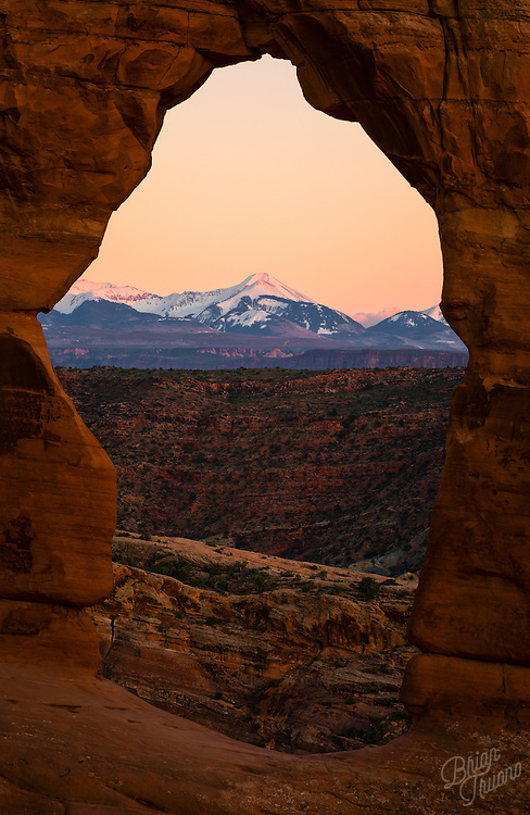 Peering through Delicate Arch at the La Sal mountains to capture the day's remaining alpine glow.