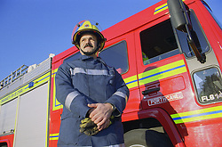 Part time male firefighter standing in front of fire engine wearing uniform,