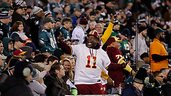 Behind the end zone a Redskin fan with DeSean Jackson's No. 11 jersey celebrates amongst eagles fans.<br /> <br /> Check elsewhere on this site for all images of this shoot. Selected images are published as part of photo essay on WHYY's NewsWorks.org. - http://www.newsworks.org/index.php/local/item/89516-young-champions-celebrated-at-eagles-game-photos<br /> <br /> (&copy;2015, All Rights reserved - Bastiaan Slabbers/BasSlabbers.com)