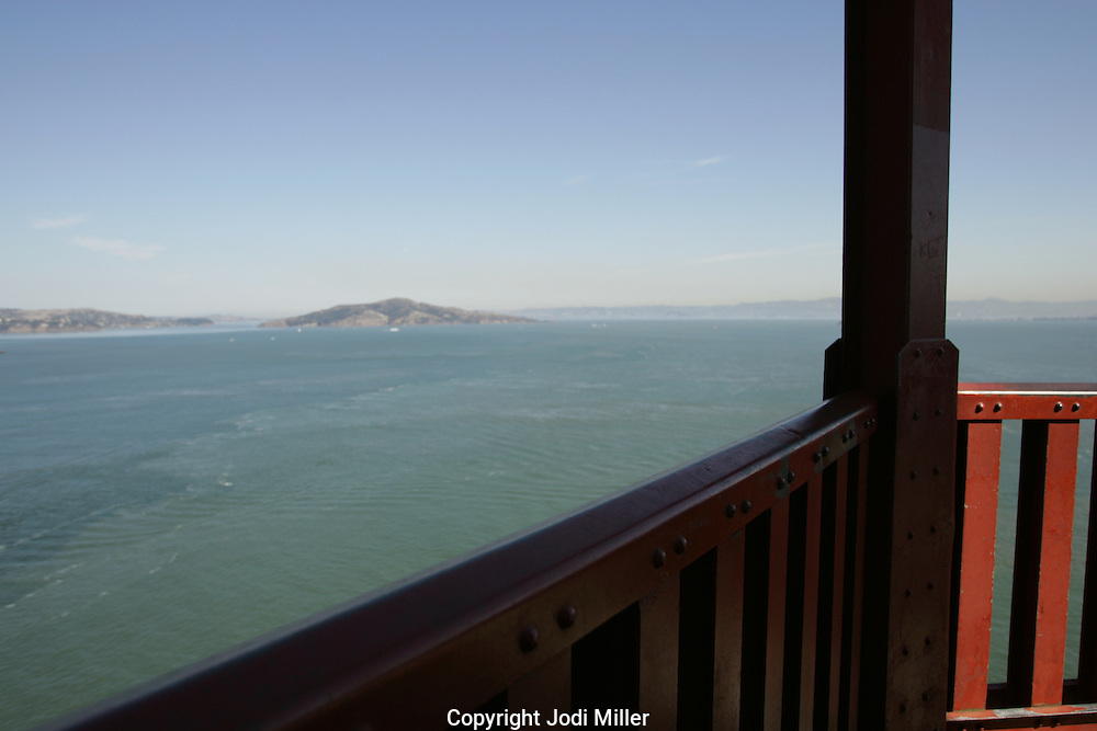 looking over a rail of the Golden Gate bridge.