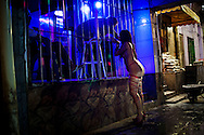 A sex worker talks to a customers at Vila Mimosa prostitution zone in Rio de Janeiro, Brazil, Thursday, May 4, 2011. <br /> <br /> Spelling the possible end of Vila Mimosa is a high-speed train the government wants to build to link Rio to Sao Paulo, as part of Brazil's Olympic proposal. The government is expected to open bidding to prospective builders July 29.
