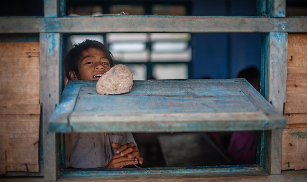 Boy looking through school window (Vietnam)