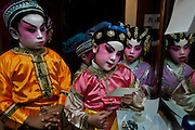 Left to right: Yogesh (10), Tsz-Ying (8), Tsoi-Yan (8) of Cha Duk Chang are reading the MC script before a performance.<br /> <br /> Cha Duk Chang (查篤撐) is a Children's Cantonese Opera Association from Hong Kong that aim is to use the traditional art of Chinese Opera as a method of education and to maintain interest in traditional culture among Hong Kong's children.<br /> <br /> At the very end of 2013, the children of Cha Duk Chang performed in Foshan, in the Guangdong province of China, a new original Opera written by Stella Ma, playwright and director of the association, called &quot;Rehearsing for a Great Fun Show&quot;. Unlike traditional Cantonese operas, this opera is designed for children. Its music and lyrics are easier to sing and to memorize.