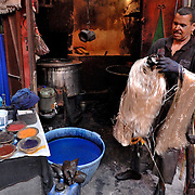 This is a silk dyeing factory in the medina (old city) in Marrakech, Morocco.  They prepare the dyes and drop the silk into large vats of dye.