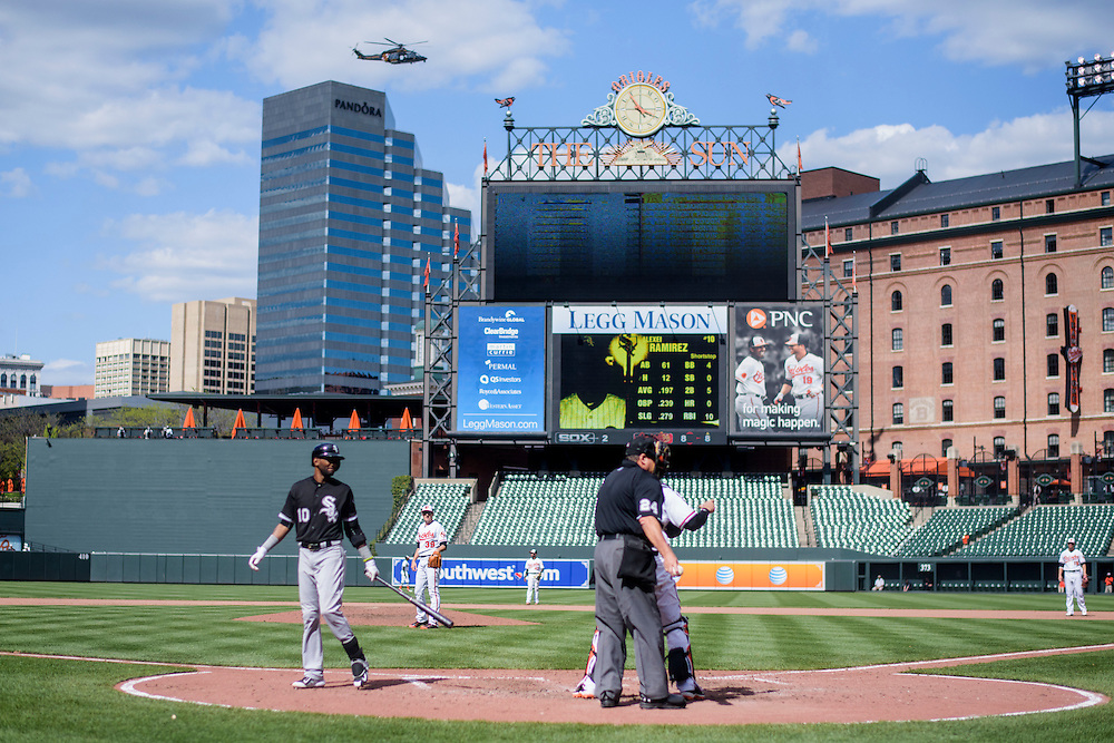 Baltimore, MD - April 29, 2015: A helicopter approaches the makeshift National Guard staging area at the shared stadium parking lot for Camden Yards and M&T Bank Stadium as White Sox shortstop Alexei Ramirez strikes out looking in the 8th inning at an empty Oriole Park at Camden Yards on April 29, 2015. It was starting Orioles pitcher Ubaldo Jimenez 7th strikeout of the game. He racked up 8 for the day. The civil unrest in Baltimore has forced the game between the Chicago White Sox and Baltimore Orioles to be closed to the public and moved to the afternoon. (Matt Roth for ESPN)
