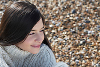 Young woman smiling sitting on beach close-up