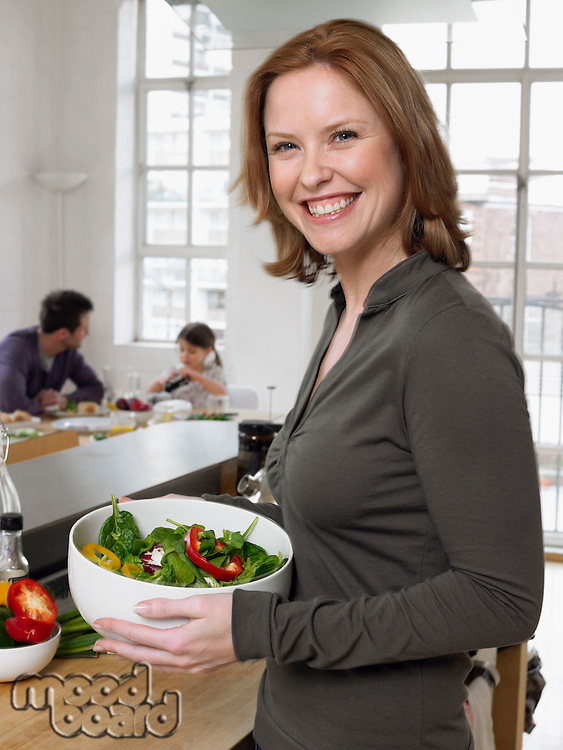 Woman holding salad bowl in kitchen (portrait)