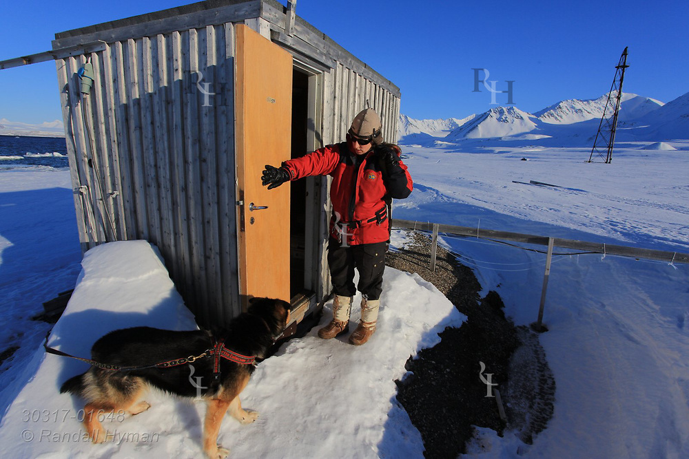 Woman checks research shed amid April snows at the international science village of Ny-Alesund on Spitsbergen island in Kongsfjorden; Svalbard, Norway.