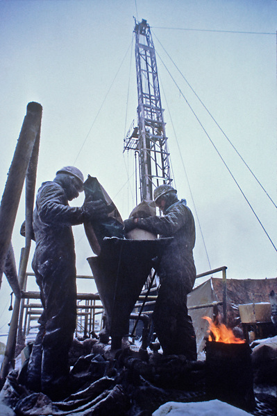 Stock photo of two roughnecks mixing drilling fluids on a oil and gas rig in Colorado during the winter.