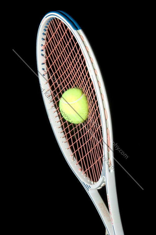 A Tennis Ball hitting a Racket .  Note the deformation of both the tennis ball and the tennis racket.  The ball has a velocity of approximately 20 meters per second in this image.  This image was photographed using high speed flash to freeze the motion taking place in 1/15,000th of a second.