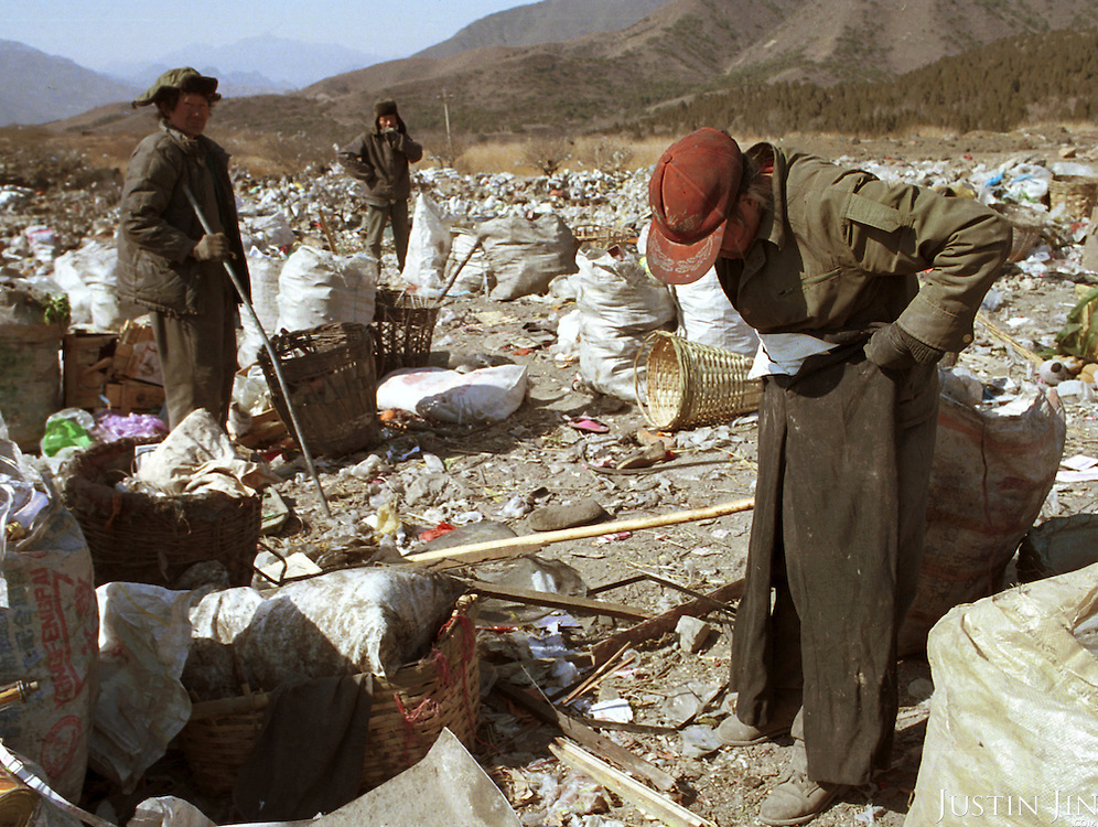 A Sichuanese worker in her 30s inspects a pair of trousers she found among the garbage...Picture taken March 1999.Copyright Justin Jin
