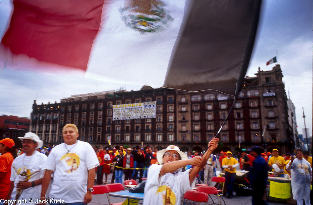 jku032303048 - 30 JULY 2002 - MEXICO CITY, DF, MEXICO: A woman waves a Mexican flag on the Zocalo in Mexico City's historic center in Mexico City, July 30, 2002 before the Pope's arrival in Mexico to canonize Juan Diego. The Pontiff, making his fifth trip to Mexico, officially made Diego, the Mexican Indian who first saw the image of the Virgin of Guadalupe in 1531, a saint during a mass in the Basilica of Guadalupe July 31, 2002. Juan Diego is now known at Saint Juan Diego.  PHOTO © JACK KURTZ  RELIGION  INDIGENOUS  CULTURE  PATRIOTISM
