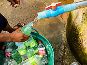 10 MAY 2016 - TA TUM, SURIN, THAILAND: A man fills recycled soft drink bottles with water from the artesian well in Ta Tum, Surin, Thailand. The well is the most important source of drinking water for thousands of people in the communities surrounding it.  In the past many of the people had domestic water piped to their homes or from wells in their villages but those water sources have dried up because of the drought in Thailand. Thailand is in the midst of its worst drought in more than 50 years. The government has asked farmers to delay planting their rice until the rains start, which is expected to be in June. The drought is expected to cut Thai rice production and limit exports of Thai rice. The drought, caused by a very strong El Nino weather pattern is cutting production in the world's top three rice exporting countries:  India, Thailand and Vietnam. Rice prices in markets in Thailand and neighboring Cambodia are starting to creep up.    PHOTO BY JACK KURTZ