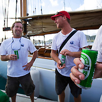 Crew from the yacht Altair relax with couple of beers after the first day of racing at the Antigua Classic Yacht Regatta. This event  is one of the worlds most prestigious traditional yacht races.