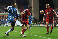 Photo: Paul Greenwood.<br />Wigan Athletic v Liverpool. The Barclays Premiership. 02/12/2006. Wigan's Fitz Hall kicks the ball and mud past Liverpool's Craig Bellamy towards Dirk Kuyt.