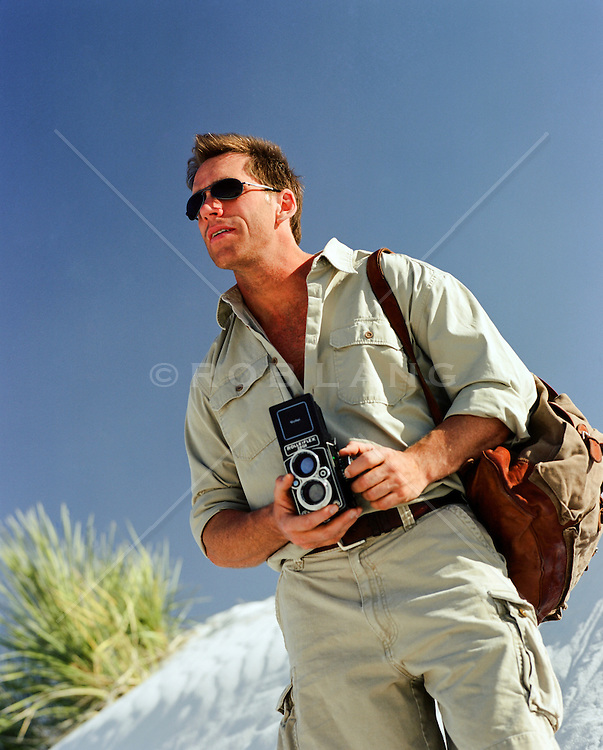 man hiking in the desert and photographing with a twin reflex camera