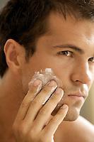Close-up of young man applying shaving cream