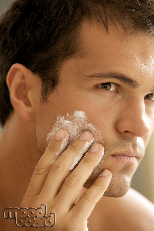 Close-up of young man applying shaving cream