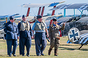 Re-enactors in period RAF costume pass WW1 bi-planes - Duxford Battle of Britain Air Show at the Imperial War Museum. Also commemorating the 50th anniversary of the 1969 Battle of Britain film. It runs on Saturday 21 & Sunday 22 September 2019