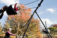 """9 Novembre, 2008. Brooklyn, New York.<br /> <br /> Dei genitori spingono i propri figli sull'altalena del parco giochi di Prospect Park a Park Park Slope, Brooklyn, NY. Park Slope, spesso definito dai newyorkesi come """"The Slope"""", è un quartiere nella zona ovest di Brooklyn, New York, e confinante con Prospect Park.  Park Slope è un quartiere benestante che ha il maggior numero di nascite, la qualità della vita più alta e principalmente abitato da una classe media di razza bianca. Per questi motivi molte giovani coppie e famiglie decidono di trasferirsi dalle altre municipalità di New York a Park Slope. Dal punto di vista architettonico, il quartiere è caratterizzato dai brownstones, un tipo di costruzione molto frequente a New York, e da Prospect Park.<br /> <br /> ©2008 Gianni Cipriano for The New York Times<br /> cell. +1 646 465 2168 (USA)<br /> cell. +1 328 567 7923 (Italy)<br /> gianni@giannicipriano.com<br /> www.giannicipriano.com"""