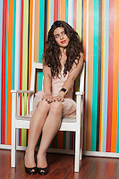 Beautiful young woman sitting on chair against colorful striped wall