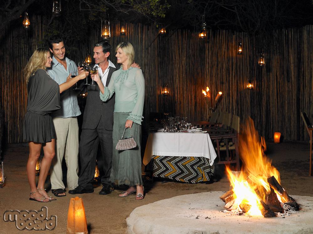 Four people toasting at outdoor nightclub near bonfire night