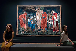 "© Licensed to London News Pictures. 22/10/2018. LONDON, UK. Staff members sit next to ""The Adoration of the Magi"", 1894, by Edward Burne-Jones.  Preview of the largest Edward Burne-Jones retrospective to be held in a generation at Tate Britain.  Burne-Jones was a pioneer of the symbolist movement and the only Pre-Raphaelite to achieve world-wide recognition in his lifetime.  The exhibition runs 24 October to 24 February 2019.  Photo credit: Stephen Chung/LNP"