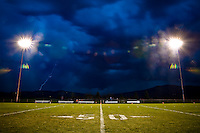 JEROME A. POLLOS/Press..Storm clouds and lightening roll across the mountains south of Post Falls and an empty football field during the first quarter of Friday's Post Falls vs. Sandpoint game. The game was delayed nearly an hour and a half due to the storm only to be cancelled after a traffic accident nearby caused the lights to go out.