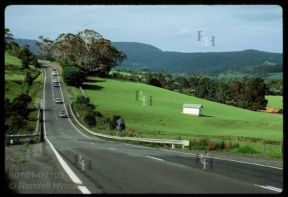 Line of cars speeds down long hill on highway nestled amid the lush pastures of Shoalhaven, NSW Australia