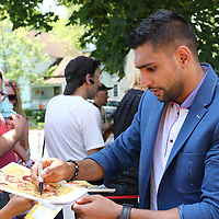 CANASTOTA, NY - JUNE 14: Boxer Amir Khan stops to sign an autograph during the parade at the International Boxing Hall of Fame induction Weekend of Champions events on June 14, 2015 in Canastota, New York. (Photo by Alex Menendez/Getty Images) *** Local Caption *** Amir Khan