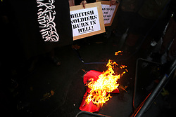 © under license to London News Pictures. 11/11/2010. Muslims Against Crusaders protesters burn a poppy, during the two-minute silence, on Exhibition Road, Kensington in London at 11am on Armistice Day.