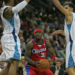 Jan 13, 2010; New Orleans, LA, USA; Los Angeles Clippers guard Ricky Davis (31) is defended by New Orleans Hornets forward David West (left) and forward Peja Stojakovic (right) during the second quarter at the New Orleans Arena. Mandatory Credit: Derick E. Hingle-US PRESSWIRE