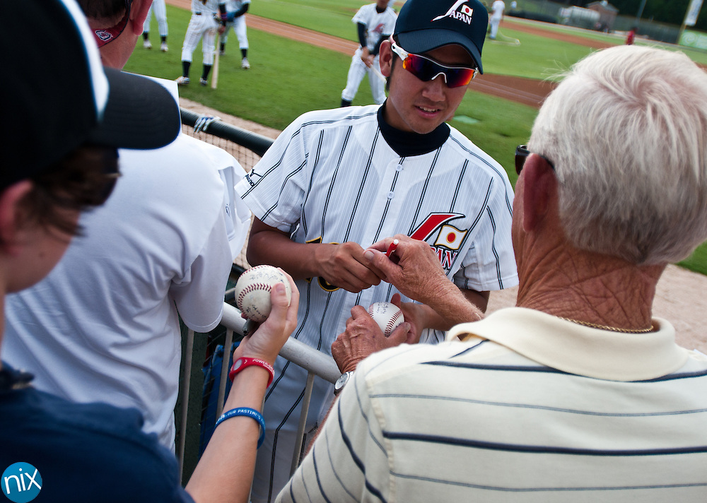 Japan's Tomoyuki Sugana signs autographs prior to the start of a baseball game between Team USA and Japan at Fieldcrest Cannon Stadium Wednesday night. (Photo by James Nix)