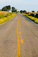 A yellow line accents the middle of a county blacktop road in rural central Illinois.