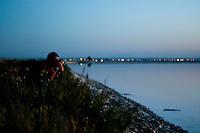 Il complesso produttivo delle saline è situato nel comune italiano di Margherita di Savoia (nome dato dagli abitanti in onore alla regina d'Italia che molto si adoperò nei confronti dei salinieri) nella provincia di Barletta-Andria-Trani in Puglia. Sono le più grandi d'Europa e le seconde nel mondo, in grado di produrre circa la metà del sale marino nazionale (500.000 di tonnellate annue).All'interno dei suoi bacini si sono insediate popolazioni di uccelli migratori e non, divenuti stanziali quali il fenicottero rosa, airone cenerino, garzetta, avocetta, cavaliere d'Italia, chiurlo, chiurlotello, fischione, volpoca.In primo piano un fotografo è intento a riprendere il tramonto sulle sponde di un bacino.