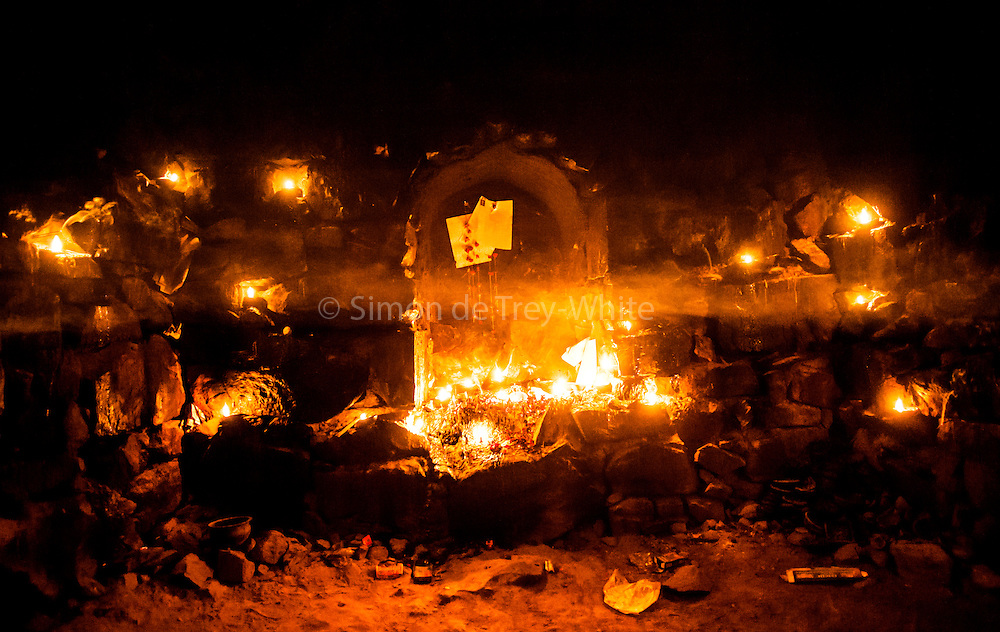 11th December 2014, New Delhi, India. Layers of smoke hang in the air in a chamber where believers pray, make offerings and ask for wishes to be granted by Djinns in the ruins of Feroz Shah Kotla in New Delhi, India on the 11th December 2014<br /> <br /> PHOTOGRAPH BY AND COPYRIGHT OF SIMON DE TREY-WHITE a photographer in delhi<br /> + 91 98103 99809. Email: simon@simondetreywhite.com<br /> <br /> People have been coming to Firoz Shah Kotla to leave written notes and offerings for Djinns in the hopes of getting wishes granted since the late 1970's. Jinn, jann or djinn are supernatural creatures in Islamic mythology as well as pre-Islamic Arabian mythology. They are mentioned frequently in the Quran  and other Islamic texts and inhabit an unseen world called Djinnestan. In Islamic theology jinn are said to be creatures with free will, made from smokeless fire by Allah as humans were made of clay, among other things. According to the Quran, jinn have free will, and Iblis abused this freedom in front of Allah by refusing to bow to Adam when Allah ordered angels and jinn to do so. For disobeying Allah, Iblis was expelled from Paradise and called &quot;Shaytan&quot; (Satan).They are usually invisible to humans, but humans do appear clearly to jinn, as they can possess them. Like humans, jinn will also be judged on the Day of Judgment and will be sent to Paradise or Hell according to their deeds. Feroz Shah Tughlaq (r. 1351&ndash;88), the Sultan of Delhi, established the fortified city of Ferozabad in 1354, as the new capital of the Delhi Sultanate, and included in it the site of the present Feroz Shah Kotla. Kotla literally means fortress or citadel.