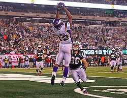 Oct 11, 2010; East Rutherford, NJ, USA; Minnesota Vikings wide receiver Percy Harvin (12) catches a touchdown over New York Jets safety Jim Leonhard (36) during the second half at the New Meadowlands Stadium. The Jets defeated the Vikings 29-20.