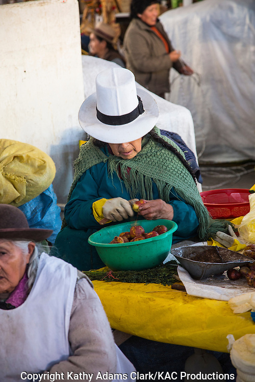 Lady in traditional dress in Cusco, Peru. Hat denotes village or region. Peeling potatos in the market.